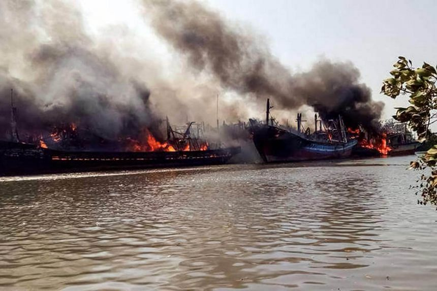 Smoke rise up from the blaze of traditional fishing boats in Pati, Central Java province, on July 15, 2017, as fire services are struggling to put out the billowing blaze at a riverside port on the northern coast of Java island.