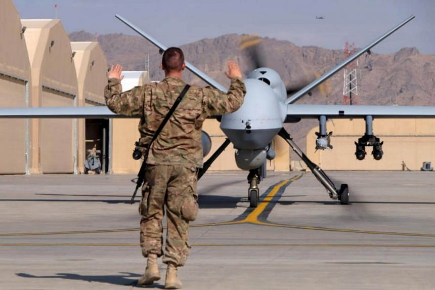 A US airman guides a US Air Force MQ-9 Reaper drone as it taxis to the runway at Kandahar Airfield, Afghanistan, on March 9, 2016.