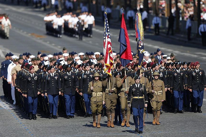US troops, led by soldiers in US combat attire from World War I, marching in the Bastille Day parade in Paris yesterday. The French government traditionally invites a country of honour to lead the parade, which is linked to a historical event and hig