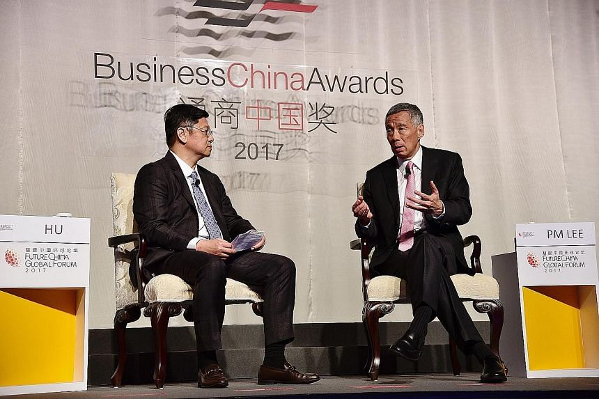 "Prime Minister Lee Hsien Loong speaking at the dialogue session of the FutureChina Global Forum yesterday, with moderator Robin Hu, board director of Business China, beside him. On China's Belt and Road initiative, Mr Lee said it is an ""open, welcomi"