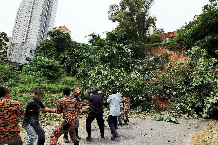 Firemen helping to clear a fallen tree after a landslide yesterday morning in George Town, Penang.