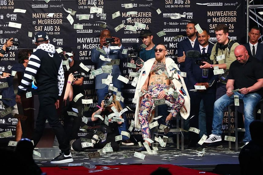Floyd Mayweather walks away from a jeering Conor McGregor (wearing floral trousers) after showering the Irishman with dollar bills at the Barclays Centre in New York on Thursday, during their four-stop tour.