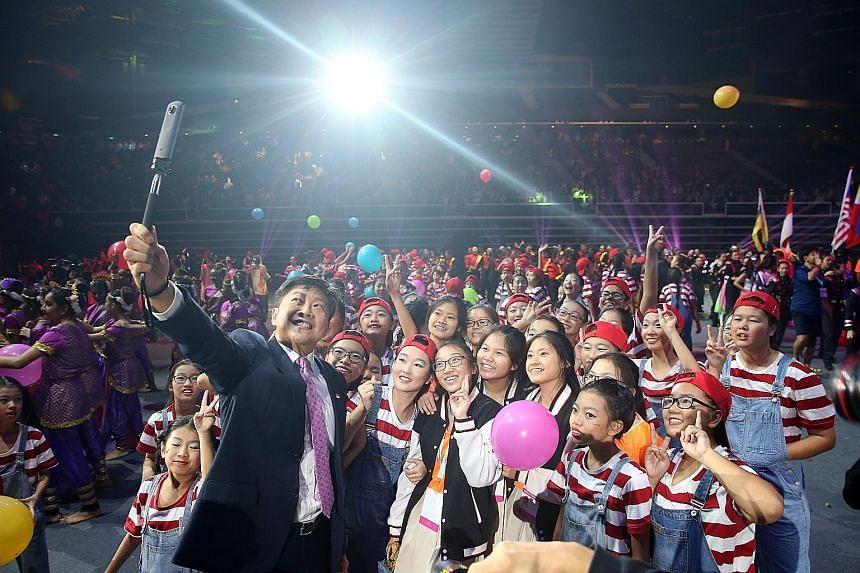 Above: The Singapore contingent at yesterday's march-past. Left: Minister Ng Chee Meng taking a wefie with performers.