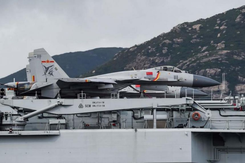 J-15 fighter jets are seen on the flight deck of China's sole aircraft carrier, the Liaoning, as it arrives in Hong Kong waters, less than a week after a high-profile visit by Chinese President Xi Jinping on July 7, 2017.