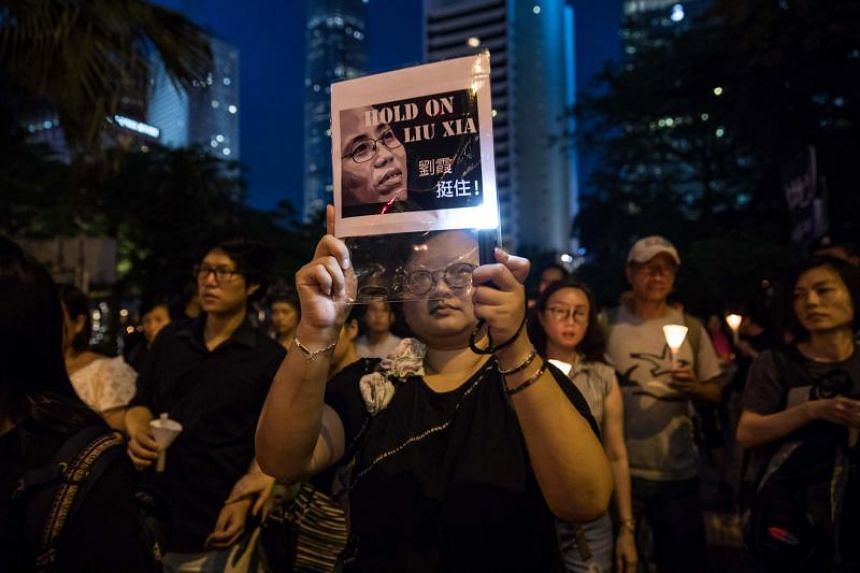 People attend a candlelight march for the late Chinese Nobel laureate Liu Xiaobo in Hong Kong on July 15, 2017.
