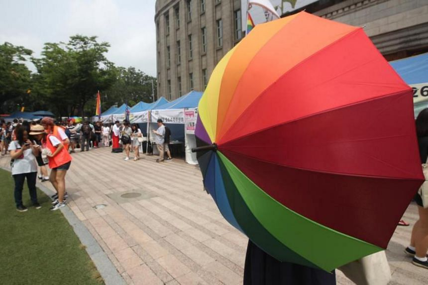 A participant in the 18th Korea Queer Culture Festival holds a rainbow umbrella - symbolic of lesbian, gay, bisexual and transgender and intersex people - at Seoul Plaza in central Seoul, South Korea, on July 15, 2017