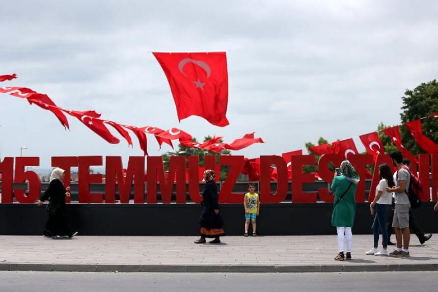 People posing in front of a huge display that reads '15 July Epic' in Istanbul, Turkey, on July 14, 2017.
