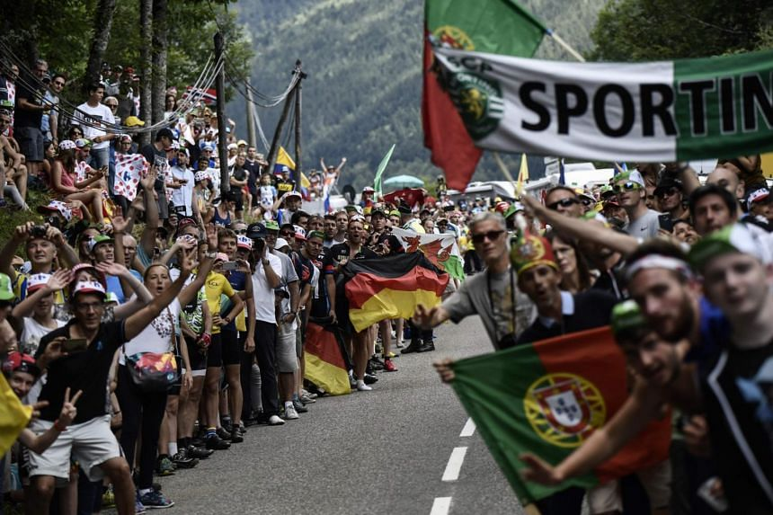 Supporters cheer along the road during the 101km thirteenth stage of the 104th edition of the Tour de France cycling race, on July 14, 2017.
