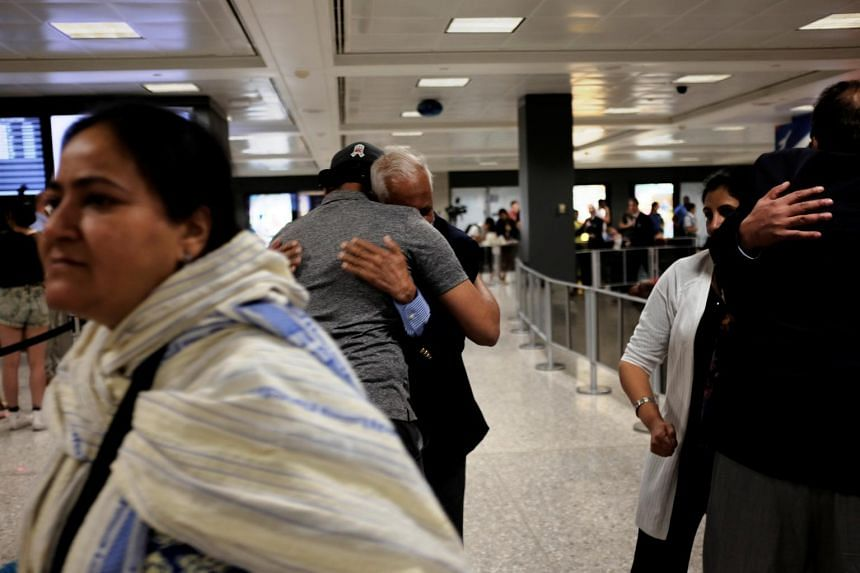 International passengers embrace family members as they arrive at Washington Dulles International Airport in Dulles, Virginia, US, on June 29, 2017.