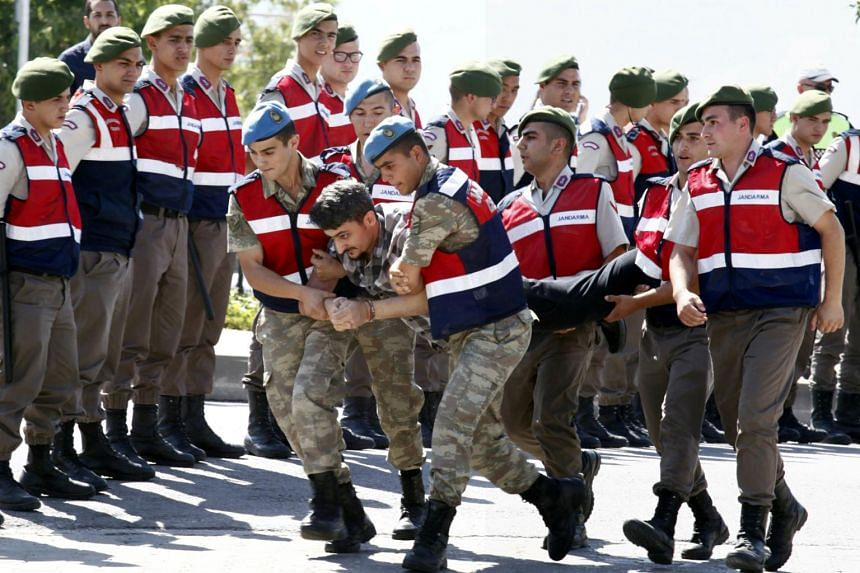 A soldier accused of attempting to assassinate Turkish President Tayyip Erdogan on the night of the failed July 15, 2016 coup is carried by gendarmes to the courthouse in Mugla, Turkey, on July 14, 2017.