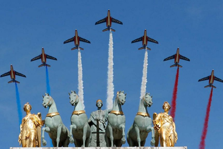 Alpha jets from the Patrouille de France, the French Air Force's precision aerobatic demonstration team, flying over the Arc de Triomphe du Carrousel during the traditional Bastille Day military parade in Paris yesterday.
