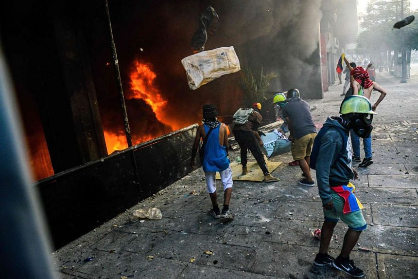 Anti-government demonstrators attack the administration headquarters of the Supreme Court of Justice as part of protests against President Nicolas Maduro in Caracas, on June 12, 2017.