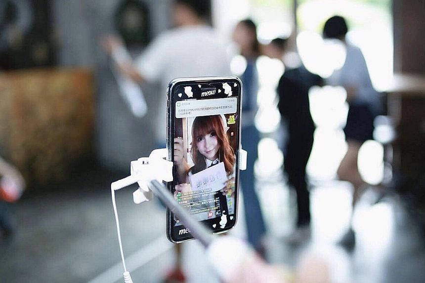 Above: Online host Zhang Xiaoxi starts her day every day in front of her mobile phone talking to hundreds of online viewers, including taking them through her daily routine of putting on make-up. The former model has been doing this full-time for nea