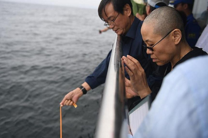 Poet Liu Xia, wife of the late Chinese Nobel Peace Prize laureate Liu Xiaobo, holding his portrait during his funeral in Shenyang, Liaoning province, yesterday. A municipal office official said the Nobel laureate's ashes (believed to be in box) were