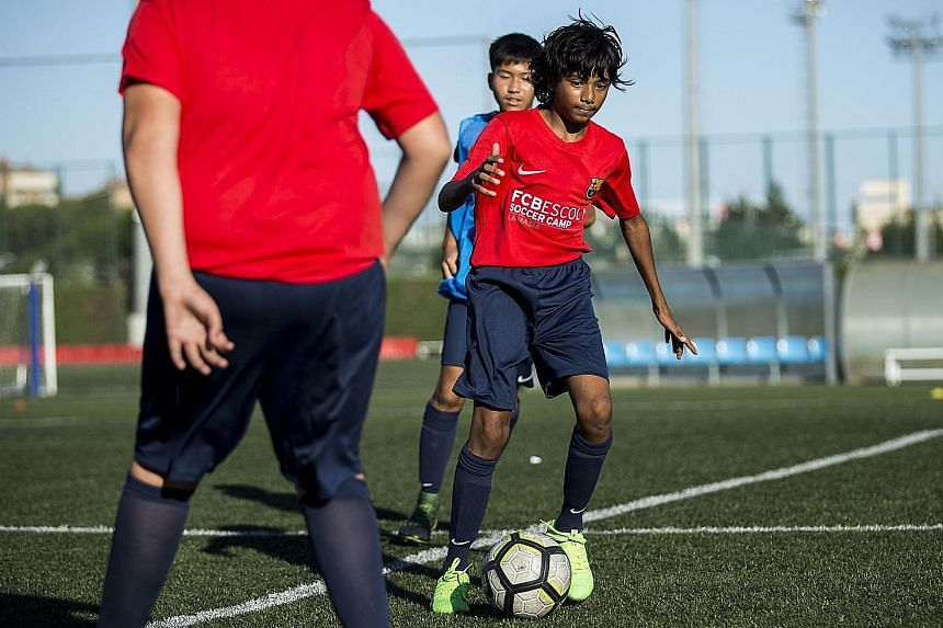 Wayne Lim (above) juggling a ball during the freestyle skills competition at the La Masia academy, while Mohammed Faizaan Shaikh practises during a training session.