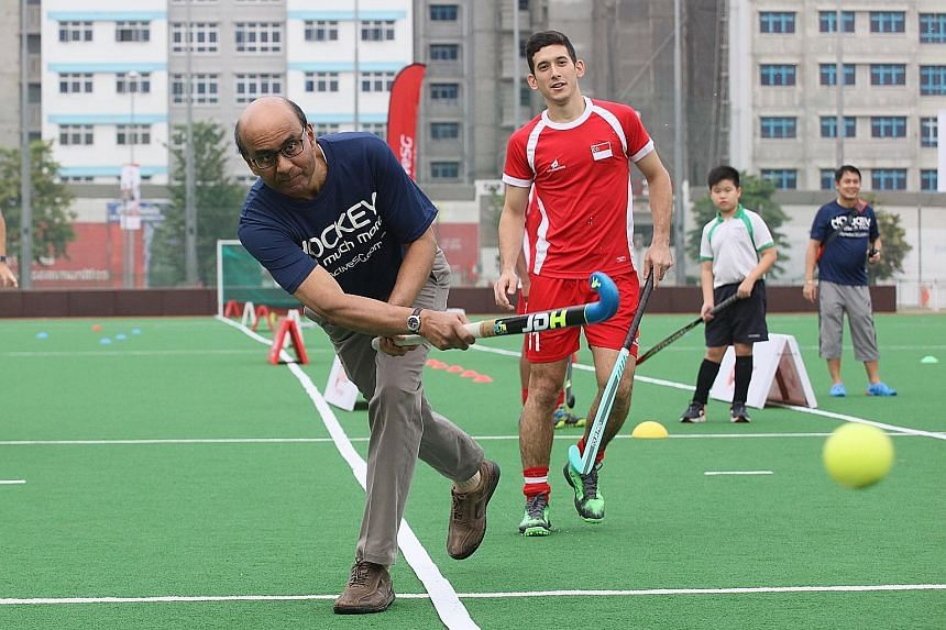 Deputy Prime Minister Tharman Shanmugaratnam taking a shot with Team Singapore hockey player Ian Vanderput looking on during the launch of the ActiveSG Hockey Academy at Sengkang Hockey Stadium yesterday.
