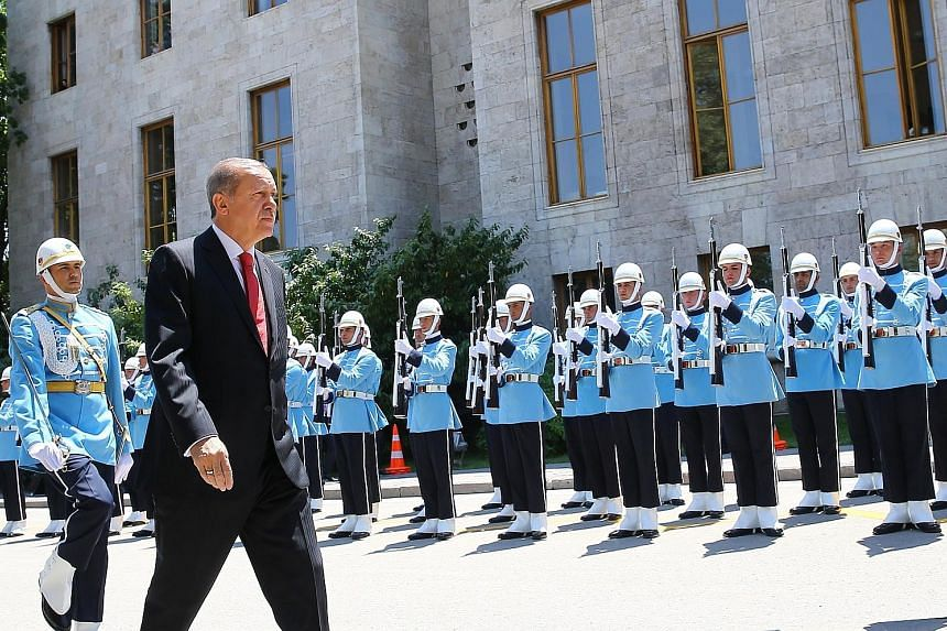 Turkish President Recep Tayyip Erdogan reviewing the guard of honour on his arrival in Ankara yesterday for a special session of Parliament, to mark the first anniversary of the failed attempt to overthrow him. Just hours before the commemorations we