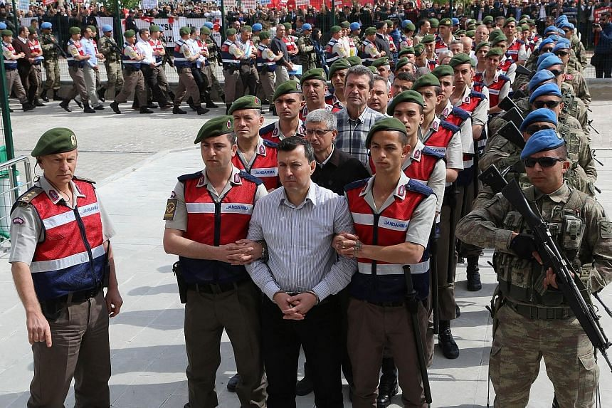 Soldiers accused of being involved in the failed coup being escorted by Turkish soldiers to court in May.