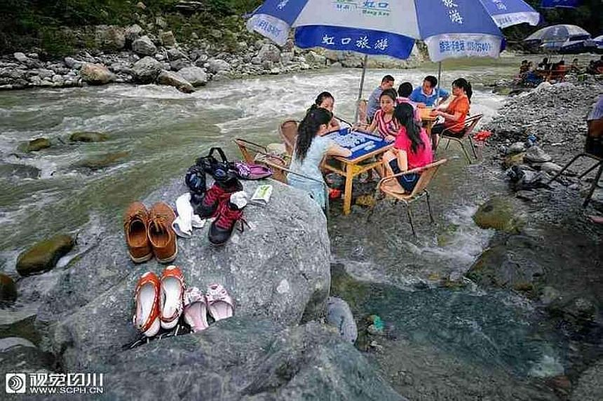 A photo posted online showing some residents of Chengdu playing mahjong in a river as a way of keeping cool during the heatwave that is affecting parts of China. Many cities have seen temperatures hit record highs.