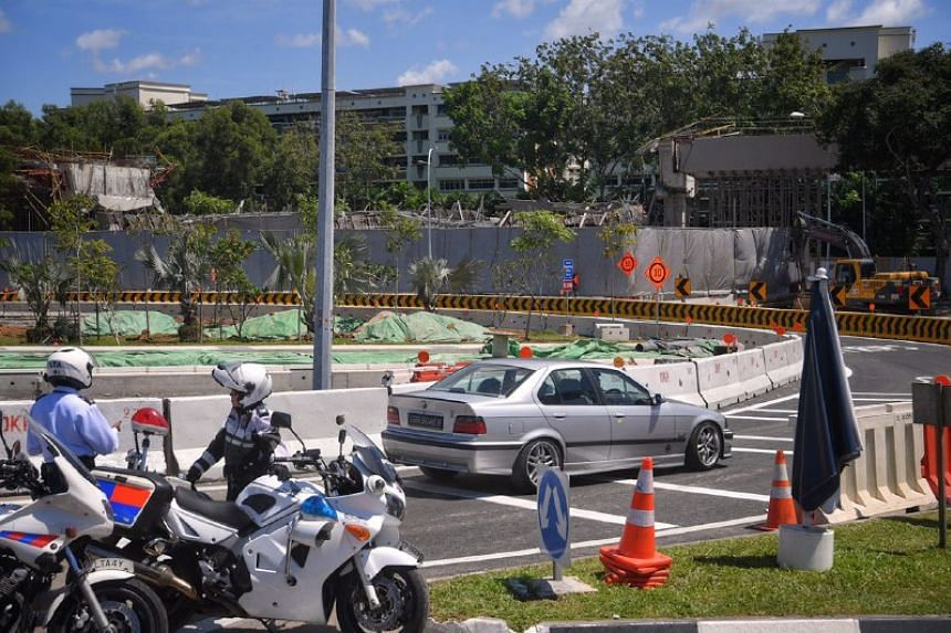 Traffic police supervise as a car travels along the temporary bypass road to connect motorists from Upper Changi Road East to Pan-Island Expressway (Changi).