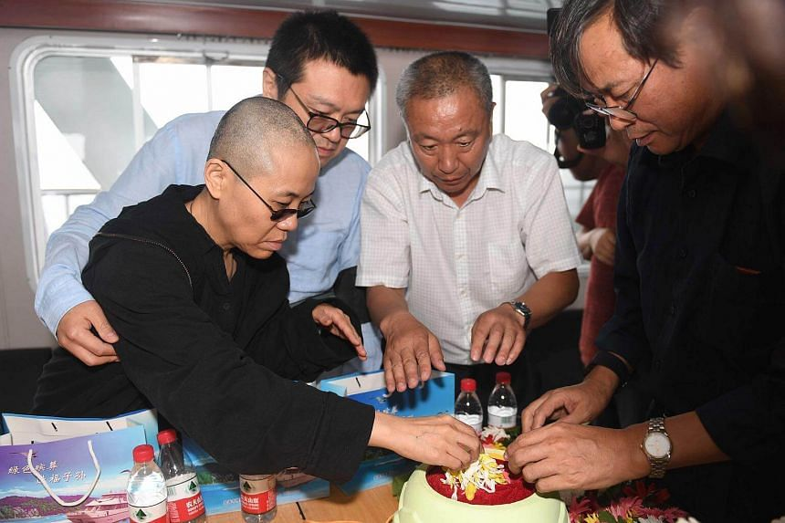 The late Nobel laureate Liu Xiaobo's wife Liu Xia (left) and her younger brother Liu Xiaoxuan (second from left), preparing flowers as they bury Liu's ashes at sea off the coast of Dalian, on July 15, 2017.