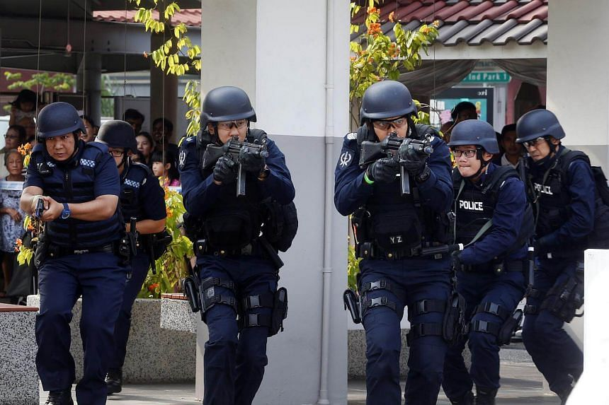 "Home Team officers moving in on a coffee shop being attacked by armed ""terrorists"" as part of an exercise on Emergency Preparedness (EP) Day in Teck Ghee on March 18, 2017."