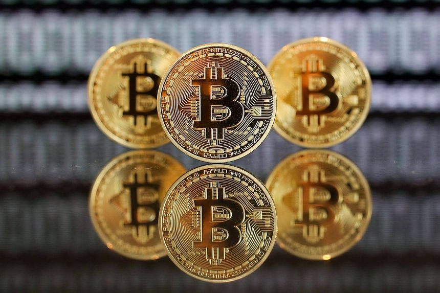 Bitcoin tokens stand in front of an illustration of binary code.