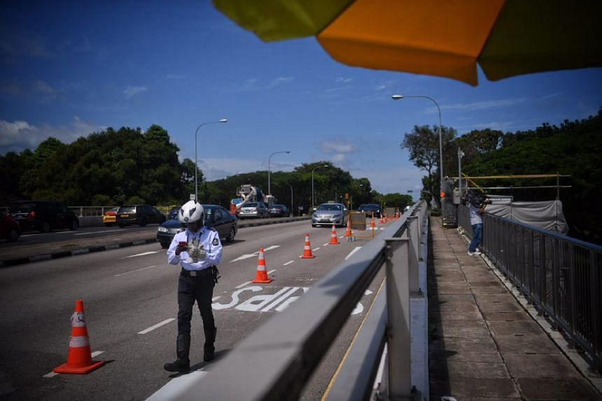 An LTA officer inspects the road before opening the temporary bypass road to connect motorists from Upper Changi Road East to Pan-Island Expressway (Changi).
