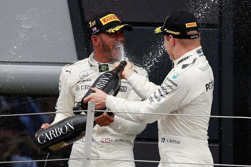 Mercedes' Lewis Hamilton celebrates his win on the podium with Mercedes' Valtteri Bottas on July 16, 2017.