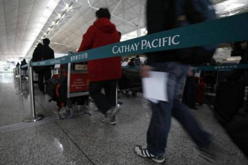 Passengers queue up at a Cathay Pacific check-in counter in Hong Kong Airport March 10, 2010.