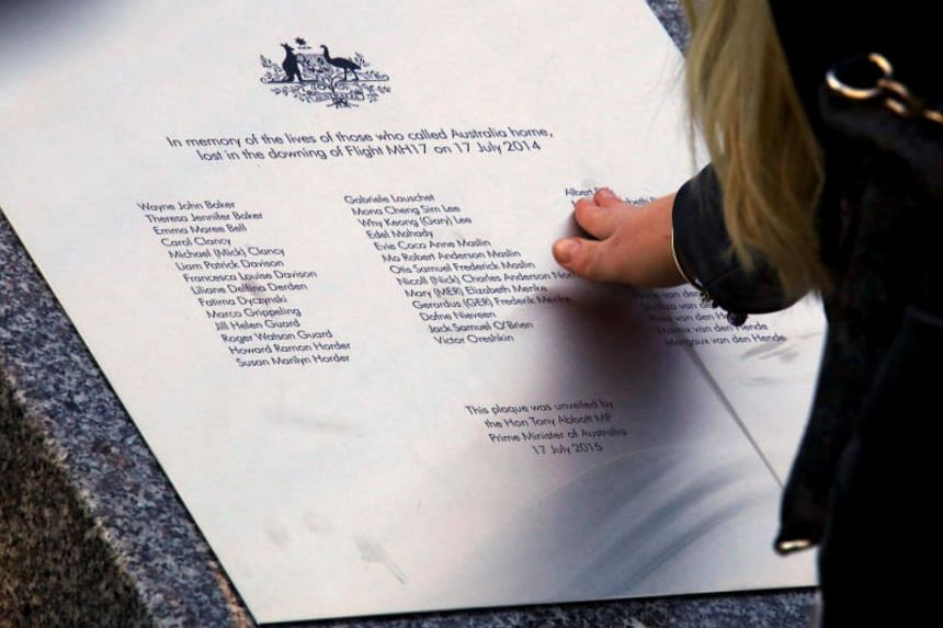 A relative of an Australian victim of Malaysia Airlines jet MH17 touches a memorial that was unveiled outside Parliament House in Canberra, Australia on July 17, 2015.