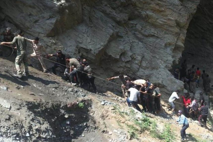 Indian police personnel and locals carry injured and dead from the site of a bus accident in Ramban district, about 140km from Jammu on July 16, 2017.