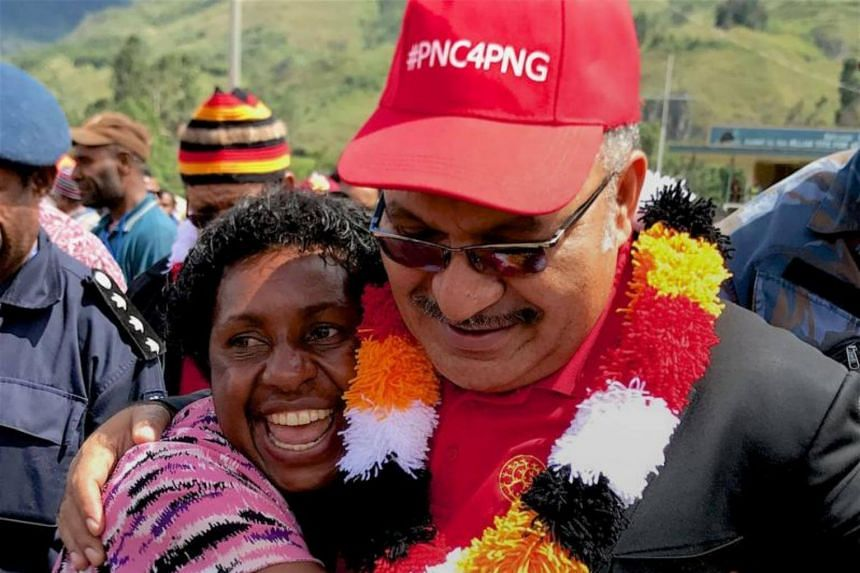 Papua New Guinea's Prime Minister Peter O'Neill (right) being embraced by a supporter as he thanks voters during a visit to the town of Mendi on July 15, 2017.