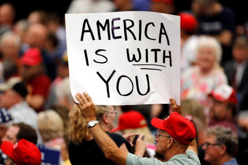 A supporter holds a sign during a rally with President Donald Trump at the US Cellular Center in Cedar Rapids, Iowa, US June 21, 2017.