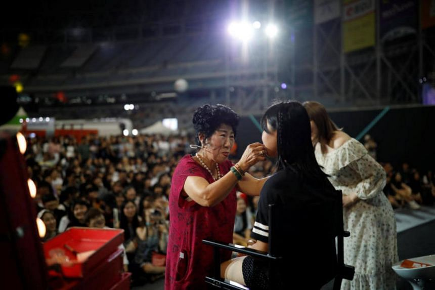 Park Mak-rye, a 70-year-old YouTuber, puts on makeup on a volunteer at a makeup show during DIA Festival in Seoul, South Korea on July 16, 2017.
