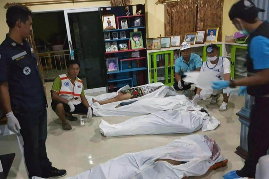 Thai rescue workers and a forensic police officer inspect bodies of a Thai family apparently murdered by gunmen at a house in the Krabi province, southern Thailand on July 11, 2017.