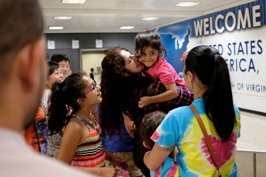 Ms Sana Tahir carries Malaika Noman, three, as the child arrives in the United States after a federal judge ruled last Thursday that President Donald Trump's temporary ban on travellers from six Muslim-majority countries cannot stop grandparents and
