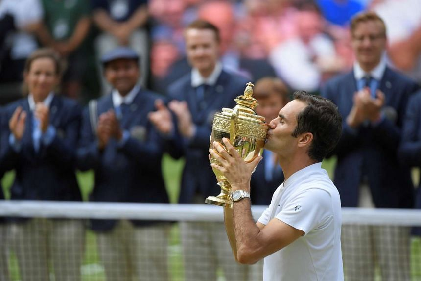 Switzerland's Roger Federer celebrates with the trophy after winning the final against Croatia's Marin Cilic on July 16, 2017.