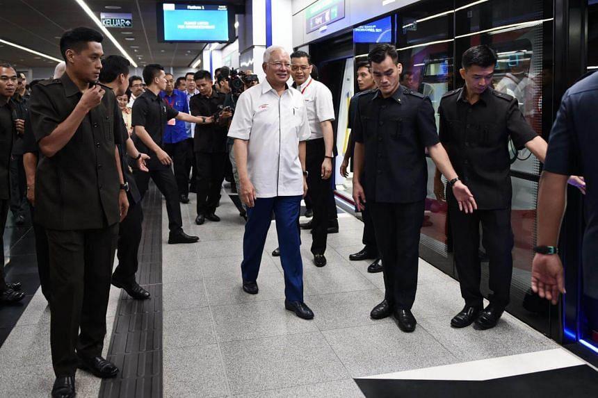 Malaysia's Prime Minister Najib Razak (centre) walks along the platform before boarding a Malaysia Mass Rapid Transit (MRT) train during the official launch of the MRT Sungai Buloh-Kajang (SBK) rail line in Kuala Lumpur on July 17, 2017.