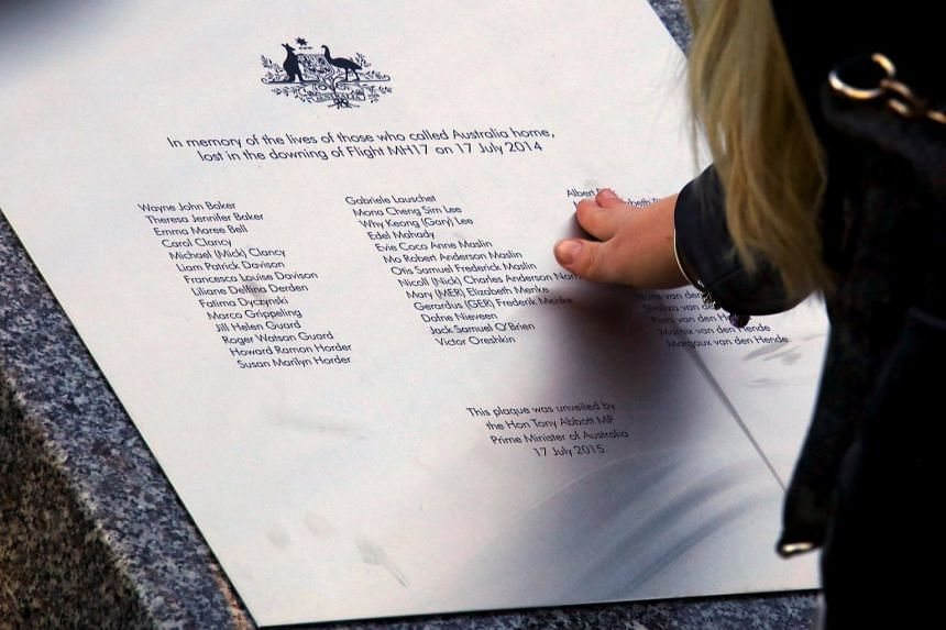 A relative of an Australian victim of Malaysia Airlines jet MH17 touches a memorial that was unveiled outside Parliament House in Canberra, Australia, on July 17, 2015.