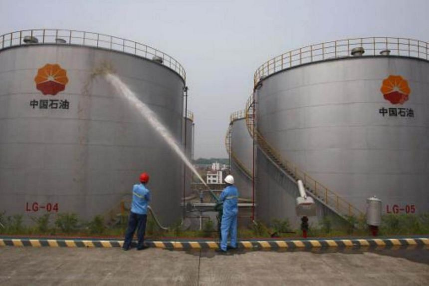 Employees spray water to cool down oil tanks at a PetroChina oil storage facility in Suijing, Sichuan Province on Aug 13, 2010.