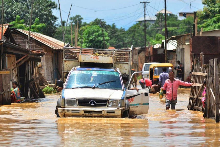 An Indian man drives his vehicle through flooded street after a heavy rainfall in Dimapur in the north-eastern state of Nagaland on July 14, 2017.