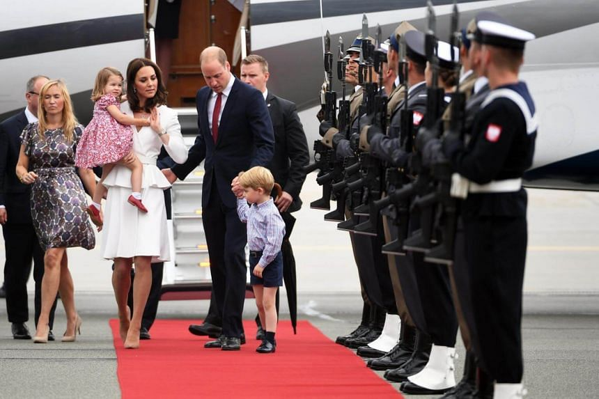 Britain's Prince William, Duke of Cambridge (right) and Catherine, Duchess of Cambridge (left) with their children Prince George and Princess Charlotte arrive at the airport in Warsaw, Poland, on July 17, 2017.