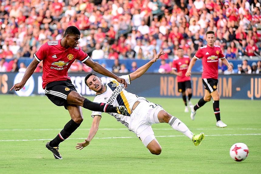 Marcus Rashford getting the better of LA Galaxy's Hugo Arellano to put Manchester United 2-0 up with his second goal. The English team won 5-2.