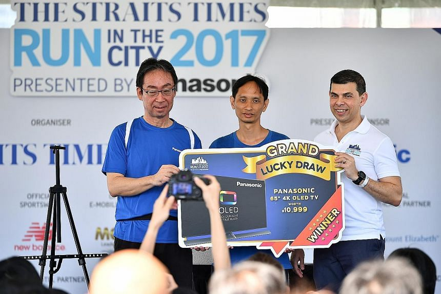 Mr Lim Beng Wei (centre) was participating in the ST Run for the first time but it turned out to be a memorable one. The 43-year-old's race bib number was picked in a lucky draw yesterday and the software engineer took home the grand prize - a Panaso
