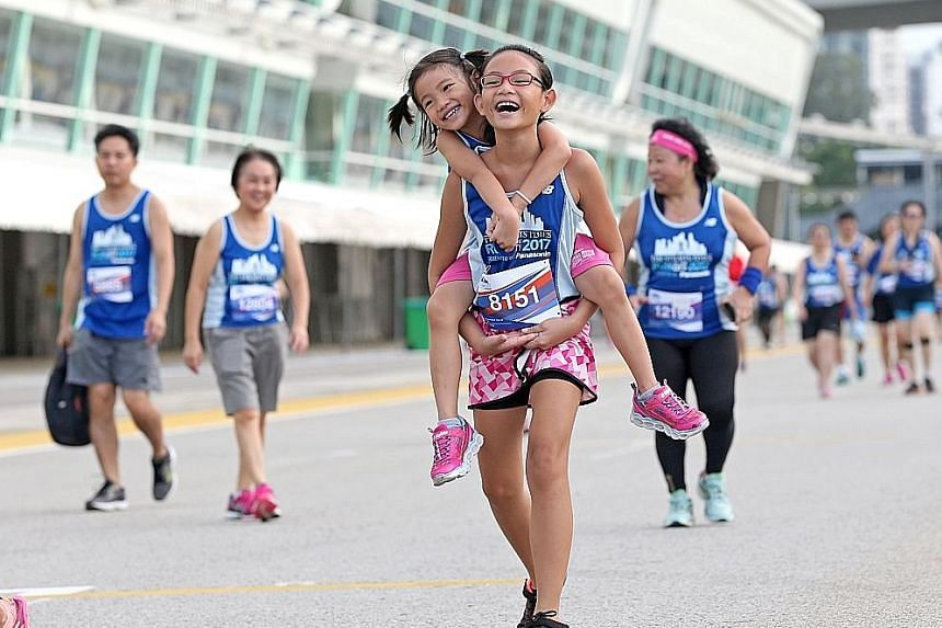 Melody Tan, 10, giving her sister Merrily, five, a piggyback ride during the 5km fun run, which they completed in 55 minutes.