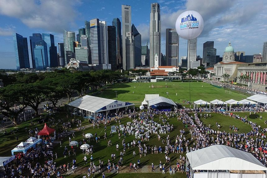 The crowd at the ST Run post-race carnival at the Padang yesterday. Musical acts entertained runners with live performances, while food vendors set up shop to feed the participants and their families and friends. Left: Runners taking photos with a Pi