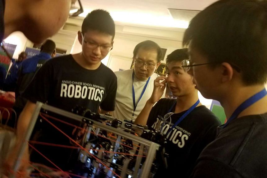 The team pondering its challenges with teacher Kenneth Wee (centre).