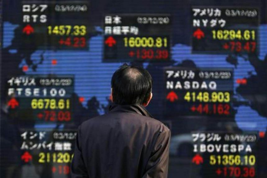 A pedestrian looks at an electronic board displaying various countries' stock market indices outside a brokerage in Tokyo.
