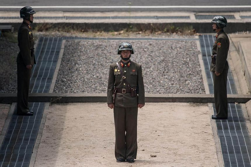Korean People's Army (KPA) soldiers stand guard before the military demarcation line separating North and South Korea at the Joint Security Area (JSA) near Kaesong.